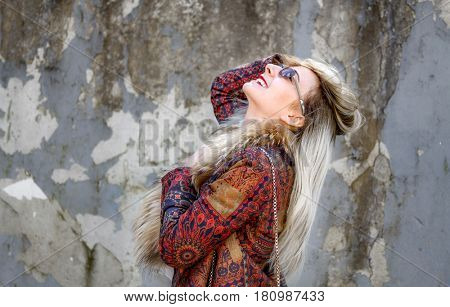 Young woman near cracked wall.