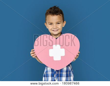 Boy hold a heart symbol in a shoot