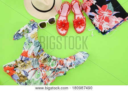 Fashion. Summer woman accessories-Summer floral clothes,,hat, shoes,sunglasses, green background
