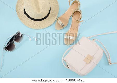 handbag clutch and Trendy Heels. Shoes,hat,sunglasses on blue background