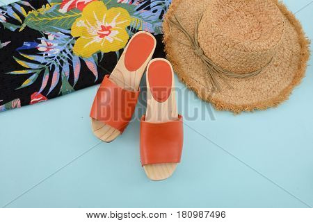 Fashion. Summer woman accessories-Summer floral scarf, wooden shoes,hat on blue background