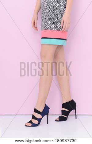 Woman in sundress . high heels.Perfect female legs -light pink background
