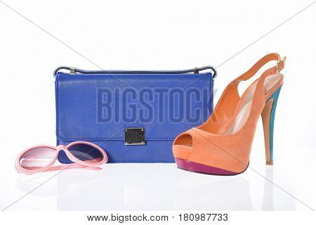 Fashion concept. Blue handbag , shoes and glasses on a white background