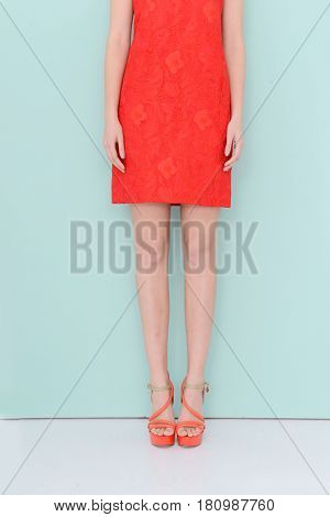 Woman in red sundress . high heels.Perfect female legs -light blue background