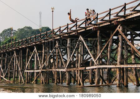 Kanchanaburi Thailand - December 09 2013: A child jumping from Saphan Mon (Mon Bridge) to Song Karia river with tourists taking photograph from the wooden bridge