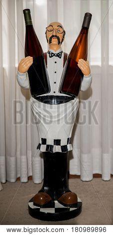 Wine holder doll holding two bottles of wine