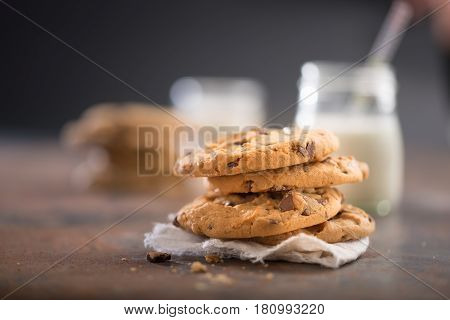 Nice image of a pile of cookies and a glass of milk on a dark warm surface.