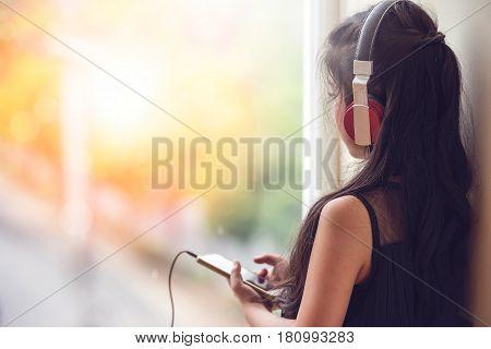 Pretty asian girl listening music with her headphones near the windowsunlight effected