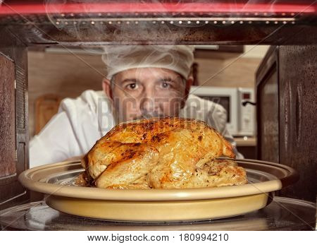 Chef prepares roast little chicken in the oven. View from the inside of the oven