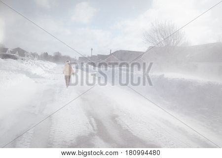 Woman out walking in a North American suburb during a blizzard.