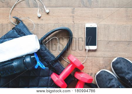 Flat lay of mobile phone water bottle towel and red dumbbells on wood background. Healthy lifestyle and Workout top view
