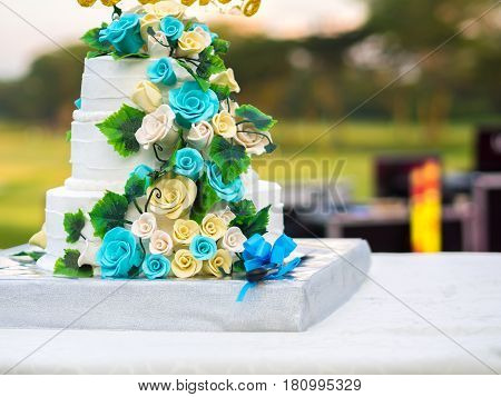Beautiful wedding cake with blue and yellow roses