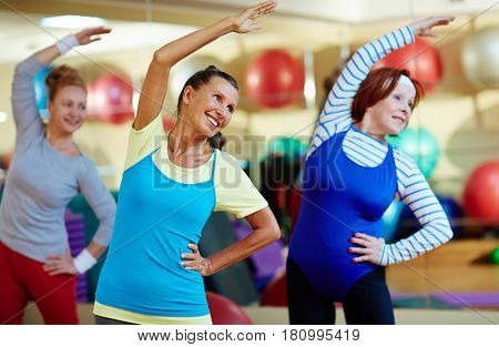 Aged women doing side-bends in gym