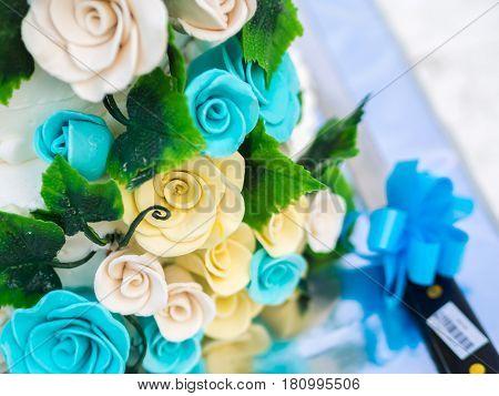 Blue and yellow roses decoration on wedding cake