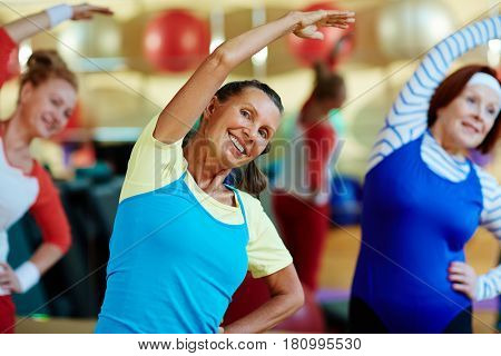 Mature energetic female stretching her arms during workout