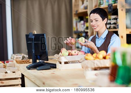 Female cashier selecting apples by workplace