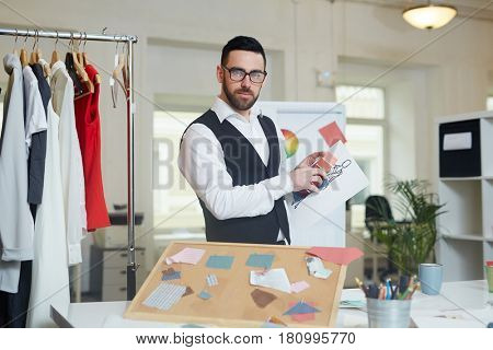 Dressmaker with sketch and palette standing by his workplace in tailoring studio
