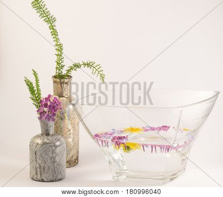 flowers floating in the bowl and two bottles