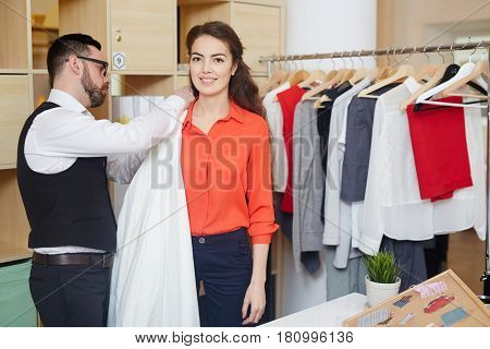 Happy female looking at camera while fashion designer choosing fabric for new dress