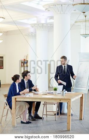 Co-workers sitting by table and talking to businessman presenting graphs on whiteboard