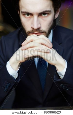 Head and shoulders portrait of handsome bearded man wearing elegant business suit, looking strongly at camera resting chin on clasped hands
