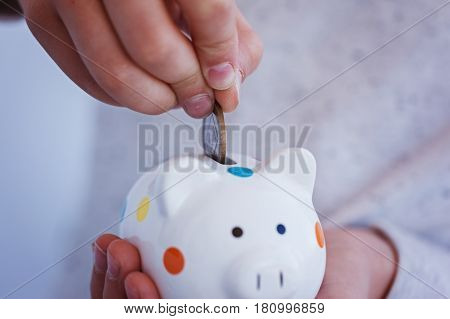 C loseup Kid hand putting coin into piggy bank or money box. Save concept.