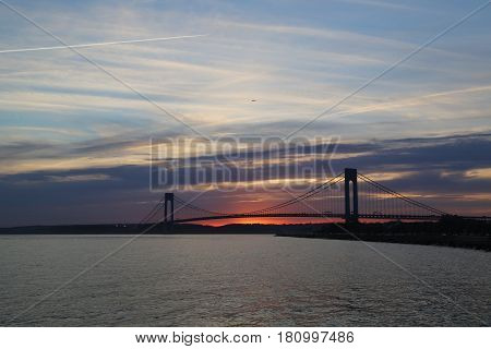 NEW YORK - APRIL 10, 2017: Verrazano Bridge at sunset in New York .The Verrazano Bridge is a double-decked suspension bridge that connects the boroughs of Staten Island and Brooklyn