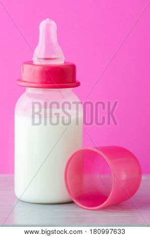 A bottle of baby milk and a nipple on a pink background close up