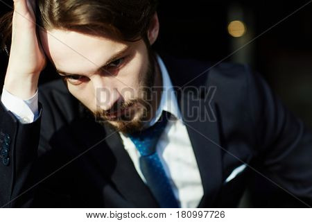 Head and shoulders portrait of handsome bearded man wearing elegant business suit, looking down with hand in his hair, tired and thinking