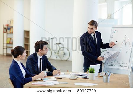Businessman explaining graph on whiteboard and consulting colleagues