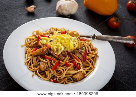 Asian noodles with chicken meat and vegetables