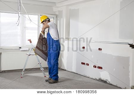 Construction worker wearing overalls and helmet carrying ceramic tile.