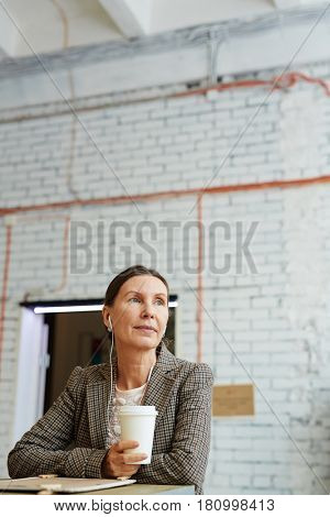Pensive female with drink thinking of what she listening to