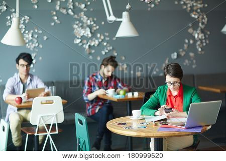 Group of young casual business people working separately in cafe, focus on young woman wearing glasses and using smartphone