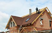 Roofing Construction and Building New Brick House with Modular Chimney Skylights Attic Dormers and Eaves. Asphalt Roofing Shingles Background. Roof Shingles - Roofing Construction, Attic construction, attic skylight, Roofing Repair. poster