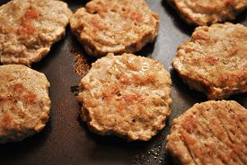 Round Breakfast Sausage Cooking on a Griddle