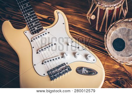 Vintage Electric Guitar And Indian Percussion Instrument (tabla) On Wooden Background.
