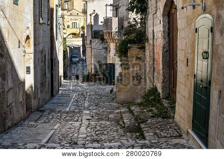 Matera, Italy - September 22 2018: A Stray Cat Is Seen At A Distance On A Shaded Back Street In The