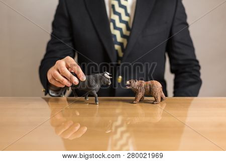 Young businessman trader holding in hands bear and bull figures. Bullish and Bearish market concept. poster