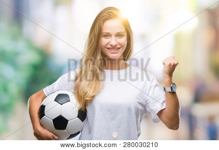 Young beautiful blonde woman holding soccer ball over isolated background screaming proud and celebrating victory and success very excited, cheering emotion