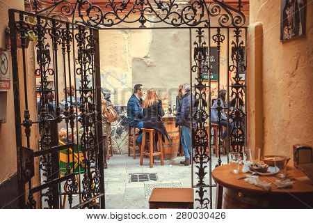 Malaga, Spain - Nov 23: Group Of Relaxing People Drinking At Outdoor Restaurant In Traditional Spani