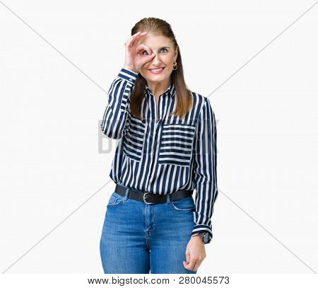 Middle age mature business woman over isolated background doing ok gesture with hand smiling, eye looking through fingers with happy face.