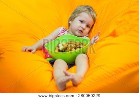 A Little Boy Wallows In An Orange Bean Bag Chair With A Green Basin Of Simple Cupcakes And Watches C