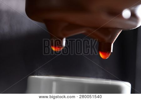Macro photo of making coffee in the coffee machine. Drops of coffee dripping into the cup