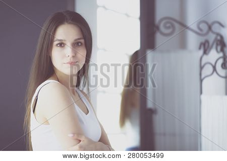 Young woman looking herself reflection in mirror at home.
