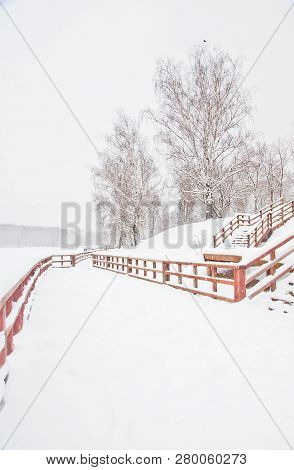 Wooden Fence In The Park In Winter