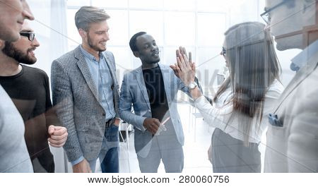 Group of young colleagues giving each other a high five