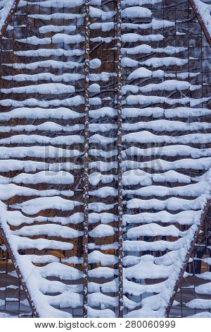 Fence Under Snow In The Park In The Evening