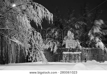 Playground And Trees In The Snow In The Evening Black And White