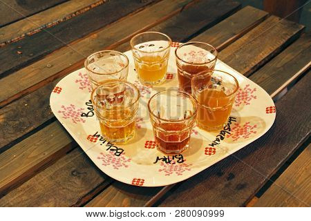 A Group Of Beer Samples In Vintage Like Glasses On A Vintage Like Plate.